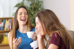 Lachen mit zwei Freunden laut zu Hause Stockbilder