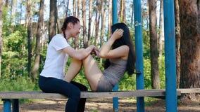 Lachen mit zwei Mädchen, das auf einer Bank sitzt stock footage