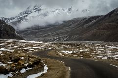 A SUV traveling through the Himalayan roads of North Sikkim near Gurudongmar Lake at 17000 ft altitude, Lachen, Sikkim, India. Lachen, Sikkim, India - 30 April Stock Photo