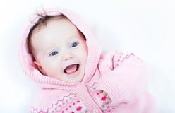 Lachend babymeisje die gebreide roze sweater met rode harten dragen royalty-vrije stock afbeeldingen