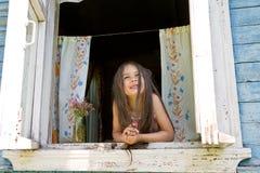 Lachend blij meisje die uit van het wijd open venster kijken royalty-vrije stock afbeeldingen