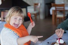 Lachend kind die chocoladecake met moeder delen Stock Afbeeldingen