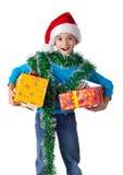 Lachend meisje in de hoed van de Kerstman met giftdozen stock fotografie