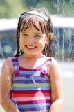 Lachend meisje in de sproeier Royalty-vrije Stock Afbeelding