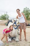 Lachend meisje die dromedariszitting in platteland en moeder omhelzen stock afbeelding