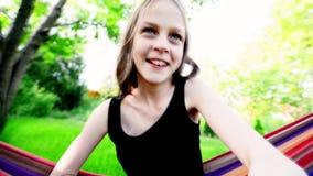 Lachend meisje die in hangmat in langzame motie slingeren stock videobeelden