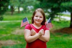 Lachend meisje die met lang krullend blond haar Amerikaanse vlag en het golven van het, openluchtportret op zonnige dag in de zom stock foto