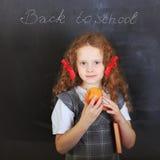 Lachend meisje met een boek en appel op zijn hand Stock Foto