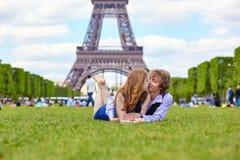 Lachend paar die op het gras in Parijs liggen stock foto's