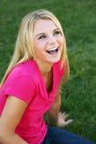 Lachend tienermeisje in gras royalty-vrije stock afbeeldingen