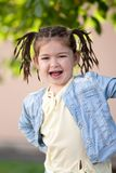 Lachend vier-jaar-oud meisje met een vlechtkapsel in een jasje Stock Fotografie