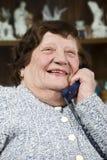 Lachende ältere Frau, die durch Telefon benennt Stockbild