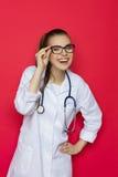 Lachende Ärztin On Red Background Lizenzfreie Stockfotos