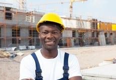 Lachende Afrikaanse Amerikaanse bouwvakker bij bouwterrein Royalty-vrije Stock Fotografie