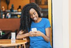 Lachende Afrikaanse Amerikaanse vrouw bij bar texting bericht met mobi royalty-vrije stock afbeeldingen