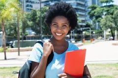 Lachende Afrikaanse Amerikaanse vrouwelijke student op campus van universiteit Stock Afbeeldingen