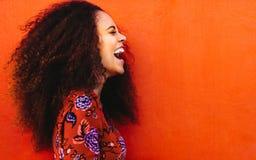 Lachende Afrikaanse jonge vrouw met krullend haar stock fotografie