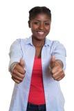 Lachende afrikanische Frau, die sich beide Daumen zeigt Lizenzfreies Stockbild