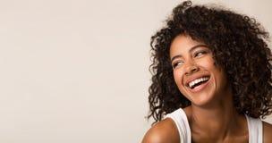 Lachende Afroamerikanerfrau, die weg auf hellem Hintergrund schaut stockfoto