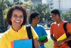 Lachende Afroamerikanerstudentin mit Gruppe anderen stu Lizenzfreie Stockfotografie