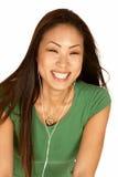 Lachende asiatische Frau mit den Ohr-Knospen Stockbilder