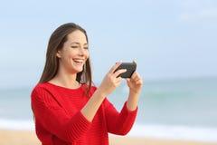 Lachende aufpassende Videos des Mädchens im intelligenten Telefon Stockfoto