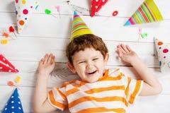 Lachende baby die op de houten vloer met feestelijke kappen en ca liggen Stock Foto's