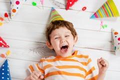 Lachende baby die op de houten vloer met feestelijke kappen en ca liggen Royalty-vrije Stock Fotografie
