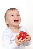 Lachende baby met rode appel Stock Afbeelding