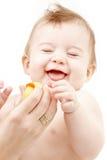 Lachende babyjongen in moederhanden met rubbereend Royalty-vrije Stock Foto's
