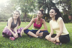 Lachende been gekruiste sportvrouwen op gras in park Stock Afbeelding