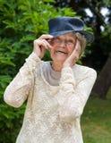 Lachende bejaarde dame die een hoed dragen Stock Foto's