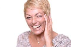 Lachende blonde erwachsene Frau, die ihr Gesicht berührt Stockbild
