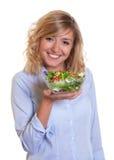Lachende blonde Frau, die frischen Salat isst Stockfoto