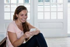 Lachende blonde Frau, die Mitteilung mit Telefon sendet Lizenzfreies Stockfoto