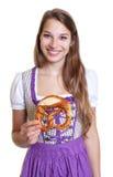 Lachende blonde Frau in einem purpurroten Kleid mit Brezel Lizenzfreie Stockfotografie