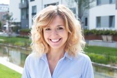 Lachende blonde Frau in einem Wohngebiet Stockfoto