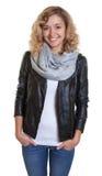 Lachende blonde Frau in einer Lederjacke Stockfotografie