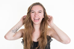 Lachende blonde Frau mit dem langen Haar, das ihr Haar berührt Stockfoto