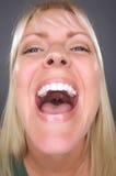 Lachende blonde Frau mit lustigem Gesicht Stockbild