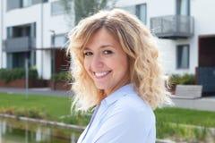 Lachende blonde Frau vor ihrer neuen Wohnung Lizenzfreie Stockbilder