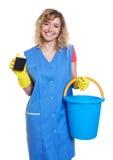 Lachende blonde Hausfrau bei der Arbeit Stockbilder