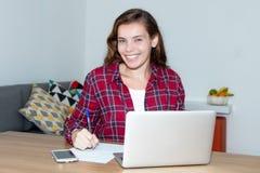 Lachende blonde Studentin, die mit Computer arbeitet Stockbilder