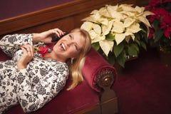 Lachende Blondine auf purpurrotem Stuhl unter Verwendung des Handys Stockfotos