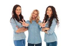 Lachende Blondine, die das Siegeszeichen nahe Freunden machen Lizenzfreie Stockfotografie