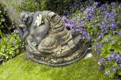 Lachende Buddha-Statue im blumigen Garten Lizenzfreies Stockbild