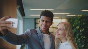 Lachende diverse medewerkers die selfie in bureau nemen Vrolijke zwarte man met het lachen het blonde vrouw nemen selfie met stock videobeelden