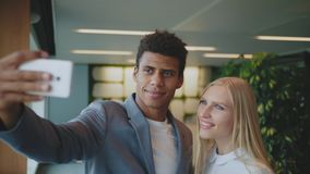 Lachende diverse medewerkers die selfie in bureau nemen Vrolijke zwarte man met het lachen het blonde vrouw nemen selfie met stock video