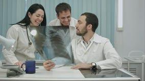 Lachende Doktoren, die Röntgenstrahl studieren stockfotografie