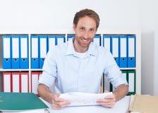 Lachende Duitse zakenman met contract op kantoor Royalty-vrije Stock Foto's